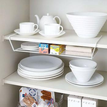 迷子になりがちな小皿は、食器棚の仕切りを利用して引っ掛けるラックにしまうと目に付きやすく便利。 食器棚上部のデッドスペースも無駄なく活用できます。
