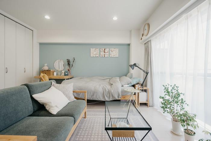このようにベッドを端に寄せ、ソファやテーブルなど作業空間を分けるよう配置すると、生活空間としてメリハリのあるレイアウトが作れます。  ワンルームで寝室とリビングを分けられなくても、ベッドが気になりにくい空間になりますよ。
