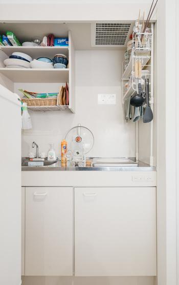 こちらの小さなキッチンでは、突っ張りタイプの棚を壁際に設置しています。調理スペースのすぐ横ではありますが、高いところにラックがあるので作業の邪魔になりません。