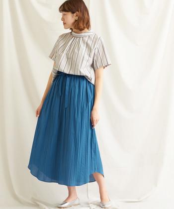 透け感が美しいブルーのスカート。ビビッドなトーンでありながらも、肌にも馴染む透明感があります。素材の軽さで上品な印象も感じられ、大人っぽい縦ストライプのトップスとも良く合っています。