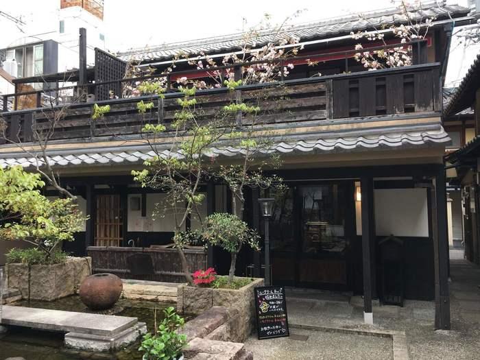 祇をん ひつじカフェは、京都市内の祇園エリアを代表する観光名所・八坂神社のすぐ近くにある町屋カフェです。風情ある建物の2階部分は料亭になっており、1階部分はカフェとなっています。