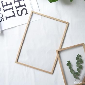 自由な使い方、飾り方ができるアクリルの額縁。使い方は、アクリル板2枚の間に写真やポスターなど飾りたいものを入れ、 木製フレームで囲み、ラバーバンドをはめるだけ。