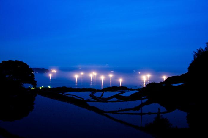 イカ釣り漁船が出港する日没後の東後畑棚田の美しさは傑出しています。日本海上に揺らめく漁火と夜空の色を映し出して紺碧に輝く棚田が織りなす景色は神秘的で思わず息をすることさえも忘れてしまうほどの美しさです。