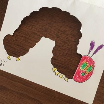 絵本のキャラクターやお子さんのお気に入りのモチーフ(恐竜や車などでもいいですね)を画用紙に描き、一部を切り抜きます。  写真のように、あおむしの体や、キャラクターのお洋服部分、車のボディなど、ある程度面積が広めになる場所を切り抜くのがオススメです。   *カッターの作業は、お母さんが担当しましょう。