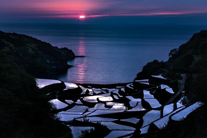 「コシヒカリ」が生産されている浜野浦棚田は、季節・時間帯によって様々な表情を見せてくれます。特に4月下旬から5月中旬にかけての夕暮れ時の美しさは傑出しています。沈みゆく夕陽、紅く染まった雲、紺碧の海、鏡のように夕暮れ空を映し出す棚田が見事に融和し、この世のものとは思えないほど素晴らしい風景を臨むことができます。