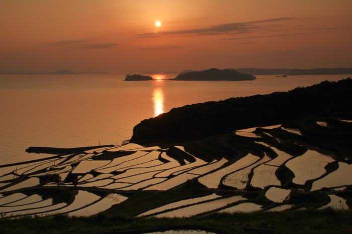 玄界灘に面して約400枚の水田が階段状に連なる土谷棚田は、日本棚田百選屈指の美しさを誇る棚田です。沈みゆく夕陽、空色を映した玄界灘、大飛島と小飛島のシルエット、緩やかな曲線を描いた棚田の畔が織りなす幻想的な風景は思わず息をすることさえも忘れてしまうほどの美しさです。