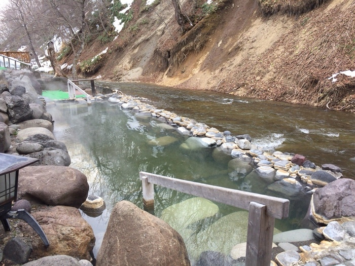 このお宿に泊まるなら、川辺の露天岩風呂は外せません。川と水位がほぼ同じで、川面に浮かんでいるかのような気分でお湯を楽しめますよ。こちらは混浴で、男女別の露天風呂も別にあります。
