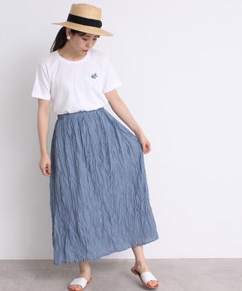 ワンポイント刺繍の入った白Tシャツを、ブルーのスカートにタックインしたコーディネートです。足元は爽やかな白のサンダルを合わせて、こなれ感たっぷりな着こなしに。