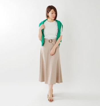 ベージュのミディ丈スカートに、白Tシャツをタックインしたコーディネートです。ベーシックカラー同士の組み合わせですが、肩からグリーンのカーディガンを羽織って程よい差し色をプラスしています。