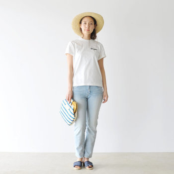 白のロゴTシャツに、薄色のデニムパンツを合わせたコーディネートです。ブルーのサンダルや青色ストライプのバッグでカラーを合わせて、ナチュラルハットで夏らしさをグッと高めた着こなしに♪