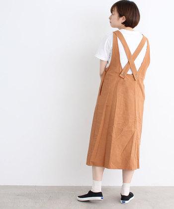 くすみオレンジカラーが印象的なワンピースに、白のTシャツをレイヤード。バックスタイルがクロスデザインになっているので、白Tシャツで露出を抑えてナチュラルに着こなしています。
