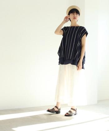 ストライプ刺繍のフレンチスリーブトップスは、ネイビーで大人っぽい雰囲気に。白のスカートとブラウンのサンダルで、シンプルに着こなしています。透け感のある白ボトムスは、夏コーデにもぴったりですね。