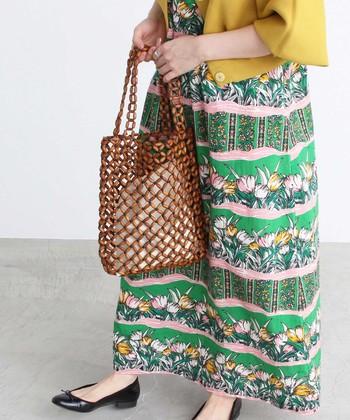 ウッドビーズを、手作業で編んで作ったトートバッグです。中が見えてしまう仕様ですが、シンプルな白巾着が付属しているので安心。カゴバッグ感覚で使える、夏らしいトートバッグですね♪