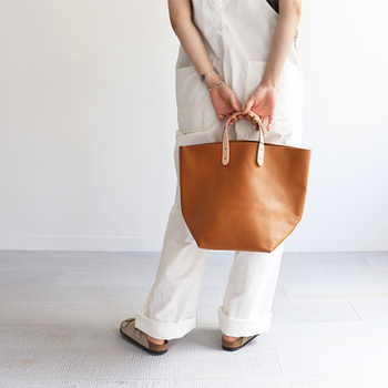程よいサイズ感のシンプルトートバッグを、シュリンプレザー素材で仕上げたアイテム。上品なキャメルカラーは、ナチュラルにもフェミニンにも合わせやすい優秀アイテムです。