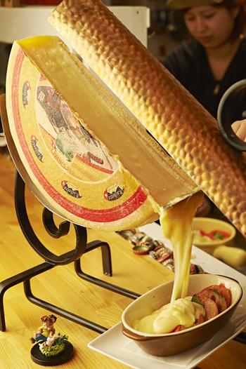 店名にもなっているラクレットチーズは、特製の機械で温められ、お料理にかかる瞬間を間近で見ることができます。バケットや野菜など、食欲をそそるメニューが並びます。