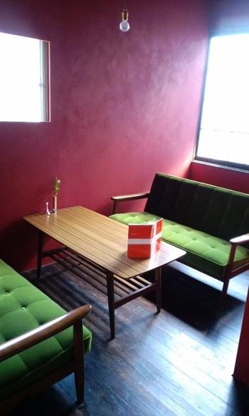 アンティーク風のソファやシンプルなテーブルが配置された2階は、赤い壁がアクセント。シックな1階とはまた違った雰囲気です。
