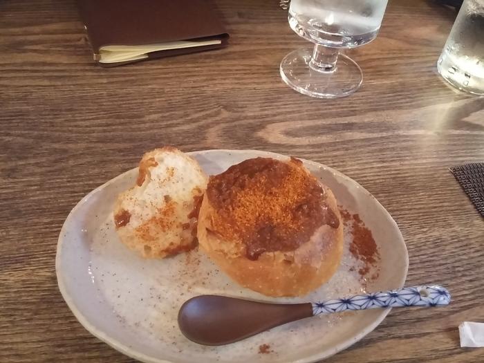 """もうひとつの定番メニューが、カレーパン。鉢状のパンの中にアツアツのカレーがたっぷり。揚げてないのでヘルシーですよ。辛さは2種類。刺激が強い「地獄のカレーパン」を完食した人の感想が書かれた""""エンマ台帳も""""必見です。"""