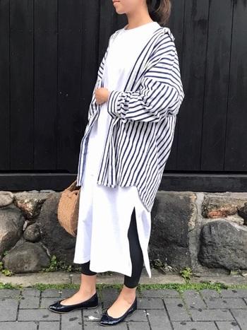 白のロングのTシャツワンピース×レギンスのレイヤードスタイルにストライプシャツで爽やかさを加えたスタイリング。色柄とゆるっとしたシルエットが涼しげです。