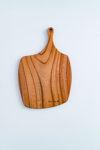 丸でもない、四角でもない形に惹かれるカッティングボード。木材の中でも比較的堅い欅(けやき)が使われているので、傷がつきにくく、持った時に少しずっしり感じる重量感が特徴です。使っていない時には、壁にかけておくだけでインテリアにもなりそうですね。  (※自然のもので製作を行っている為 色合いや木目が1つづつ異なりますことご了承ください。)