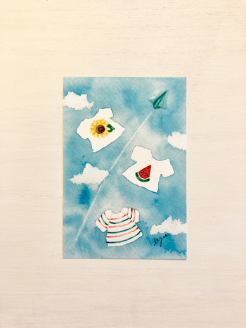 こちらは夏らしいTシャツが可愛らしい一枚。紙飛行機の飛ぶ青空は、カラッと暑い夏の日をイメージさせてくれます。お子さんがいる家庭へ送るのにも良いかもしれませんね。