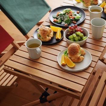 """年に一度しかキャンプをしない人は、できるだけ日用品で代用したいところですね。普段はダイニングテーブルをとして使えるテーブルを選ぶのもひとつ。 レッドオーク材を使用した「Hang out(ハングアウト)」の""""ロールトップテーブル""""。天板をクルクル丸めてコンパクトに収納可。一人暮らしや来客時にダイニングテーブルを広げたいという人にもおすすめです。"""