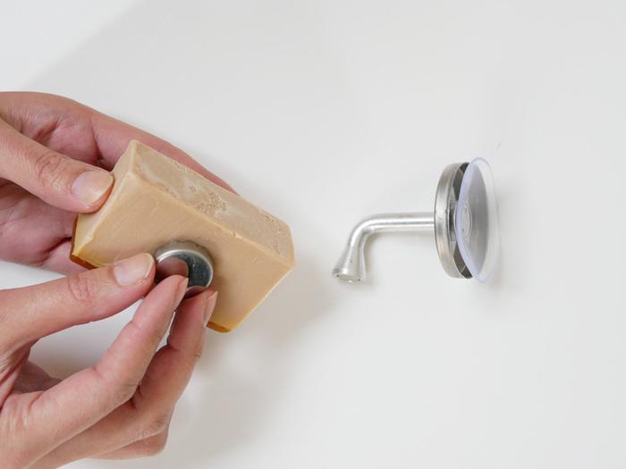秘密は石鹸に取り付けた金具と、ホルダー先端のマグネット。この二つが引き合う力で、石鹸を固定しておけるんです。本体の吸盤をお好きな場所に貼れば、簡単に石鹸の置き場所が作れますよ。