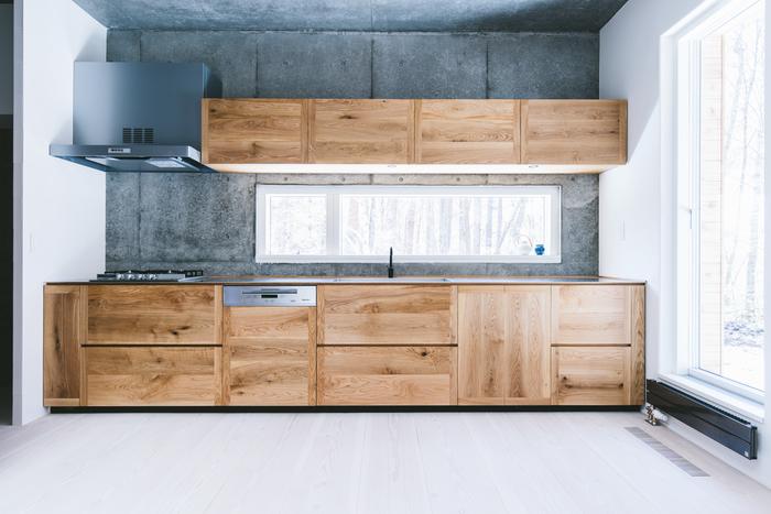 キッチンは広々としていてスタイリッシュな作り。北海道産ナラの無垢材を使用したキッチンパネルは、どう経年変化していくのか楽しみなアイテム。台所に立ちながら自然を眺められるのも良いですね。