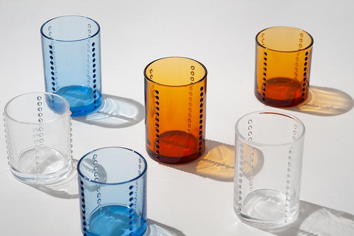 柳宗理のYグラスは四方向につけられた雫のような突起のデザインがとてもスタイリッシュ。光を受けて影を落とすと、レトロな揺らぎを感じさせてくれます。クリアなグラスはもちろん、カラーグラスも素敵です。