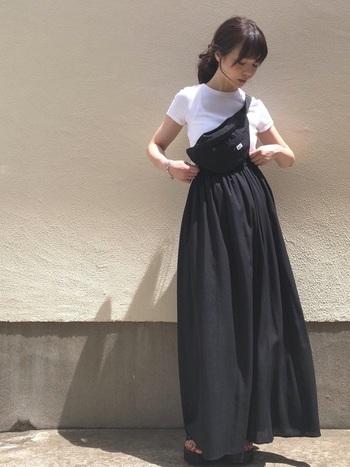 黒のマキシスカートにコンパクトな白のTシャツを合わせたスタイリング。重く見えがちな黒ボトムには、爽やかな白でコントラストをつけると、顔周りも明るい印象に。