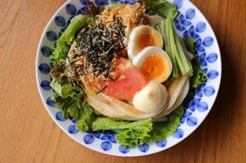 冷凍うどんと野菜をたっぷり使ったサラダうどんレシピ。鶏胸肉をイタリアンドレッシングで揉み込むのがポイント。ブルーのお皿に盛りつければ、見た目も涼やかに。