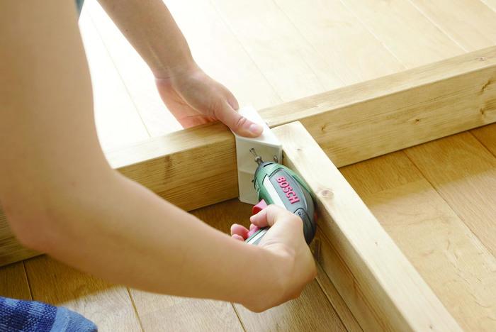 棚受けの作り付けには電動のねじ回しがあると便利。棚板の両端の裏に棚受けをネジで固定したら、支柱になる材木を通してお好みの高さに固定します。細かな計測や下準備は不要だから、思ったより簡単そう。