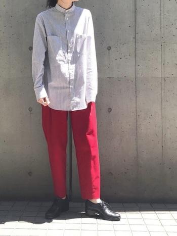 メンズライクなスタンドカラーのシャツ。袖と裾が長めのシャツをあえて折り返したりボトムスインせず、外しを加えているのがおしゃれです。