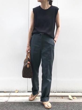 黒のノースリーブトップスにブルーグレーのパンツを合わせたラグジュアリーなスタイル。裾をラフにロールアップし、トング・サンダルで外しを加えたハンサムコーデです。