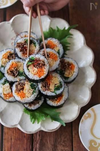 """韓国版の海苔巻き""""キンパ""""のレシピ。ごま油の風味が香ばしく、食欲をそそります。中には牛肉、ほうれん草、にんじん、卵焼きが入っていて満足感も◎。色も鮮やかなので、シンプルな麺メニューのお供にぴったりですね。"""