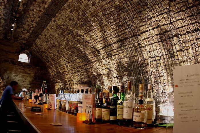Barカウンターには、様々な銘柄のウイスキーなどが無数に並んでいます。カウンターに置かれた灯りに照らされた数々のお酒の瓶は、キラキラと輝く窯の内壁と見事に調和し、落ち着いた雰囲気を醸し出している窯内部の居心地の良さを引き立てています。