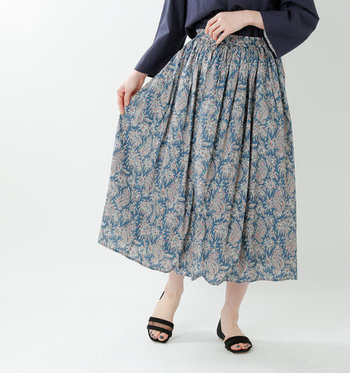 リバティ社の美しいプリントのギャザースカート。ペイズリー柄なら甘くなり過ぎずに履けます。同系色のネイビーのトップスに足元は黒のサンダルで落ち着いた印象に。
