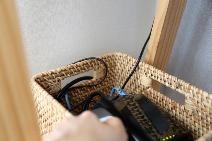ルーターと配線の収納に使用しているのは、ニトリのおしゃれな「積み重ねバスケット」です。写真のように持ち手部分の穴からコードを通して、コンセントに繋ぐことができます。
