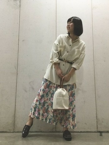 花柄のプリーツスカートには、あえてアウトスタイルで合わせたいもの。細身のベルトでウエストマークして、メリハリと女性らしさをプラス。