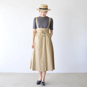 ベージュのサスペンダースカートに、グレーのトップスを合わせた着こなし。ナチュラルなハットで季節感をアピールしつつ、足元は黒のシンプルシューズで上質な大人っぽさを演出しています。