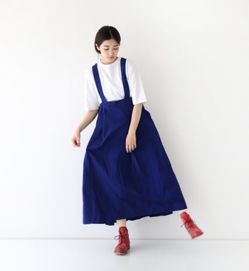 ブルーのサスペンダー付きスカートに、白のTシャツを合わせたベーシックな着こなしです。シンプルになり過ぎないよう、足元にあえてカジュアルブーツをプラス。程よいメンズ感を楽しめるコーディネートに仕上げています。