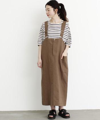 ストレートなシルエットのサスペンダー付きスカートは、同系色のボーダートップスを合わせてナチュラルな印象に。ボリューム感のある黒のサンダルをプラスすることで、程よいアクセントとトレンド感をアピールしています。