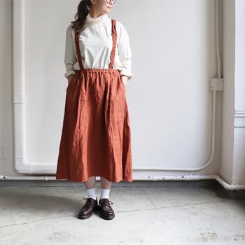 オレンジブラウンのサスペンダー付きスカートは、白トップスを合わせてナチュラルに。足元は白靴下とブラウンのローファーシューズで、マニッシュなコーディネートを演出しています。