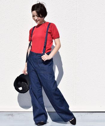 濃色のサスペンダー付きデニムパンツに、赤のTシャツとキャップを合わせたカジュアルな着こなし。メンズライクになり過ぎないよう、赤を主役にしたコーデに黒のパンプスを合わせているのがポイントです。