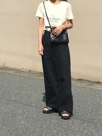 シンプルなTシャツに黒のワイドパンツを合わせたスタイル。ボトムスインで上半身をコンパクトにまとめ、パンツの丈は長めにすることで大人っぽい印象に。