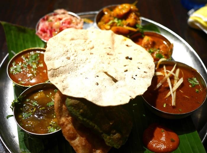 「ミールス」は、ライスやチャパティといった主食に、カレー数種、ダール、サブジ、ヨーグルト、サラダなどの副菜、アチャールと呼ばれる漬物などがセットになったインド式の定食です。 (※ミールスは、南インドの定食、北インドでは「ターリー」と呼ばれている。)  【カレー各種にスープやライスが、ワンプレートに盛り込まれた「ダバ・インディア」の『ダバ ミールス』。上にのせられたクラッカー状のものは、ひよこ豆や米粉で作られる「パパド(パーパド)」。インドやパキスタンなどの南アジア圏で広く食べられているが、南インドでは料理の付け合せとして供されることが多い。】