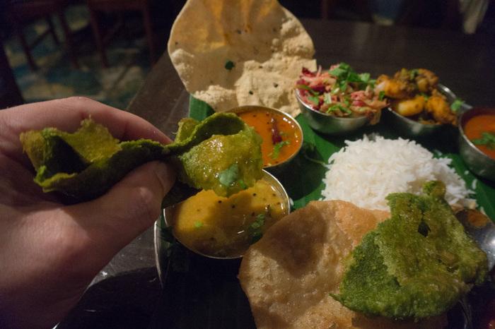 """「ミールス」の魅力は、料理一つ一つの単体の味わいにあるのではなく、その""""食べ方""""にあります。  日本ではカレー単品をご飯にかけて頂きますが、インドやスリランカ、ネパールといった南アジア圏では、ライスやパン類(チャパティやナン等)に、カリーや副菜、漬物を、徐々に""""混ぜながら頂く""""のが一般的な食べ方です。"""