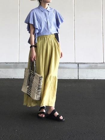 薄いブルーの袖コンシャツに、イエローのマキシ丈スカートをセット。メッシュバッグで手元もとことん夏らしく。