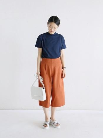 首元の立ち上がりが特徴的なTシャツとタックパンツのモードな装い。仕上げはホワイトのバッグ&シューズで軽やかに。