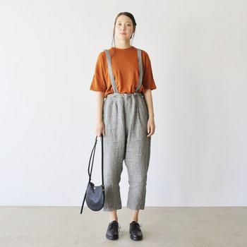 グレンチェック柄のサスペンダーパンツに、キャメル系のTシャツを合わせたコーディネート。シンプルTシャツでカジュアル見えする分、小物を黒でまとめて大人っぽくスタイリングしています。