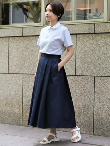 知的に見えるネイビーのロングスカートに同じくDantonのポロシャツを合わせてきれいめカジュアルに。足元は抜け感のある白のスポーツサンダルで夏らしく爽やかに仕上げています。